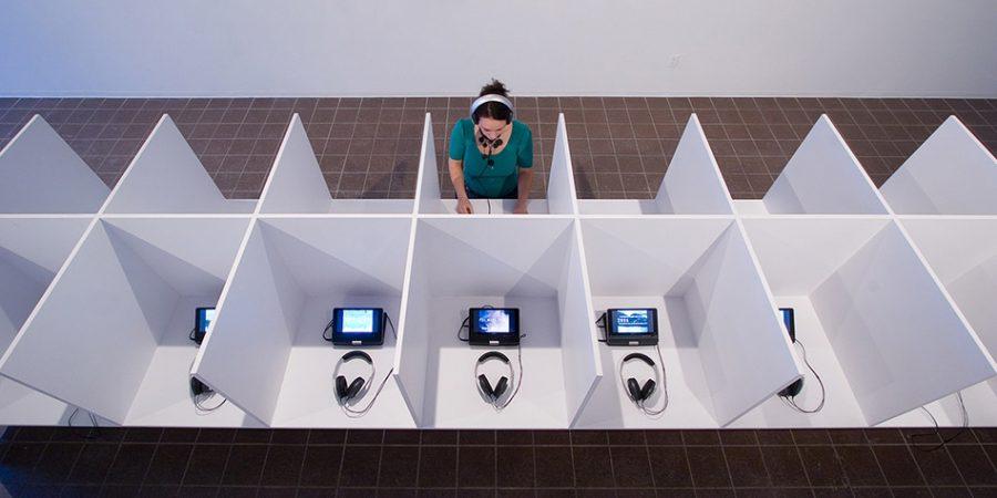 Aujourd'hui, dates-vidéos, oeuvre évolutive amorcée en 2006 (vue partielle) Installation vidéo, proposition intitulée 05.02.2006 – 05.02.2007, réalisée pour la Galerie Vox 2 structures en panneaux de fibre de pin et métal, 32 moniteurs, 32 casques d'écoute, 10 sièges sur roulettes 12.2 X 1.2 X 1.6m et 7.3 X 1.2 X 1.6m (40 X4 X5' et 24X4X5'.Photo : Michel Brunelle