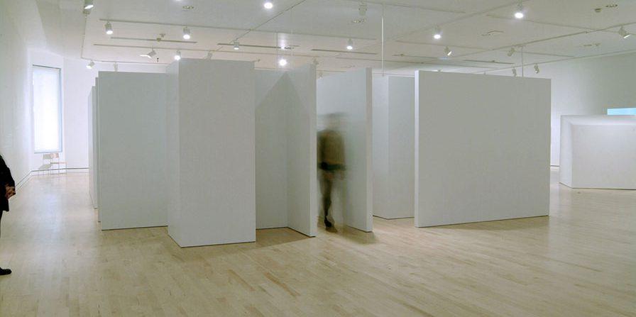 Qui se tient sur les lèvres, 2004 (vue d'ensemble) Construction architectonique, audio et vidéo Panneaux de fibre de pin, moniteur vidéo, lecteur DVD, lecteurs CD, enceintes acoustiques 8.5 X 8.5 X 2.43 m. (28' X28' X8') Photo : Ivan Binet